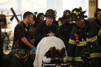 Firefighters and EMT take the injured to ambulances