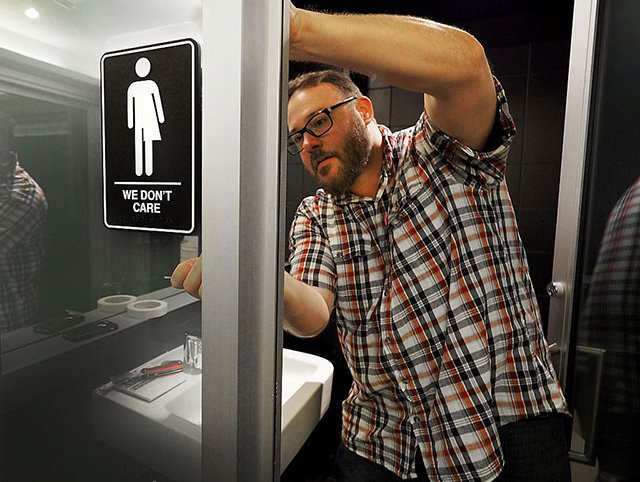 A hotel manager adheres informative backing to gender neutral signs in the 21C Museum Hotel public restrooms on May 10, 2016 in Durham, North Carolina