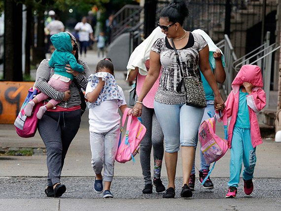 Migrant children shield their faces while leaving the Cayuga Center in East Harlem