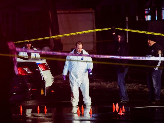 Police officers investigate the scene of the shooting in Queens
