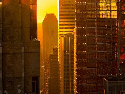 The sun shines through Manhattan buildings