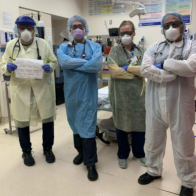 Four doctors wearing full personal protective equipment gear at St. Barnabas hospital, with their arms crossed
