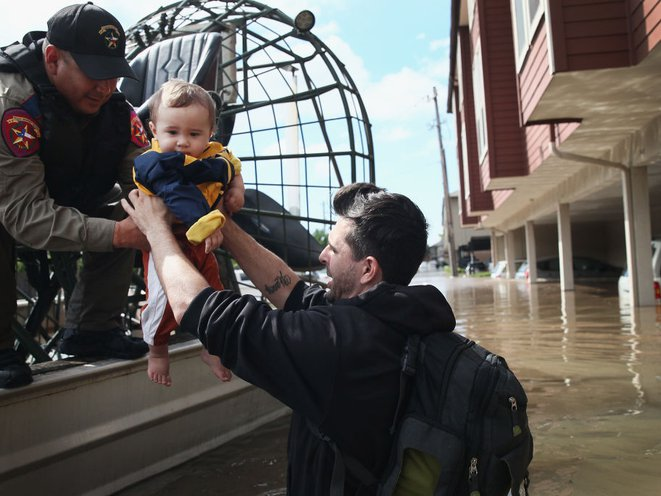 Michael Boyd passes his son Skylar over to a rescue worker as they are evacuated on an airboat from their apartment complex after it was inundated with water following Hurricane Harvey on August 30, 2017 in Houston, Texas. It was Skylar's first birthday<br>(Getty Images)