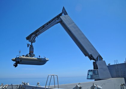 A boats and crafts crane lifts a rigid hull inflatable boat from the boat valley aboard the amphibious transport dock ship USS New York