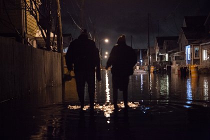 Sean O'Connell and his son Michael prepare to walk to their home through floods on 12th Road in Broad Channel, Queens.<br/>