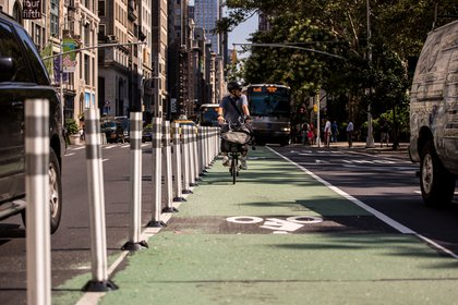 A man bikes down a newly-installed protected bike lane on 5th Avenue between West 25th and 24th Streets in Flatiron, Manhattan. The lane was given additional protection as part of the DOT's new Shared Streets redesign.</br>