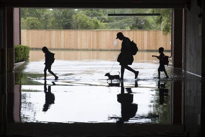 The Martinez family evacuates the apartment complex they live in near the Energy Corridor of west Houston, Texas where high water coming from the Addicks Reservoir is flooding the area after Hurricane Harvey on August 30, 2017 in Houston, Texas<br>(Getty Images)