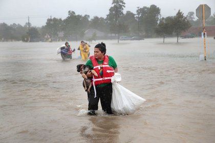 People make their way out of a flooded neighborhood after it was inundated with rain water, remnants of Hurricane Harvey, on August 28, 2017 in Houston, Texas<br>(Getty Images)