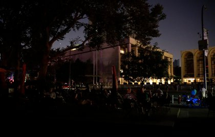People sitting in front of Lincoln Center during the blackout (JASON SZENES/EPA-EFE/Shutterstock)