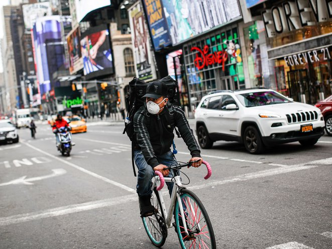 A delivery cyclist rides their bike through Times Square during the height of the pandemic in March of 2020.