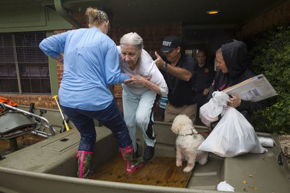 An elderly woman leaves her home and is helped into a boat after flooding caused by heavy rain during Hurricane Harvey August 29, 2017 in the Bear Creek neighborhood in west Houston, Texas<br>(Getty Images)