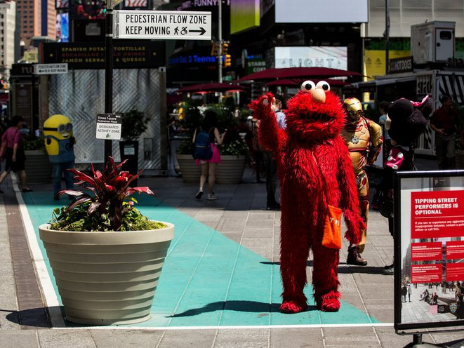 A person dressed as the Sesame Street character Elmo waves at the photographer.