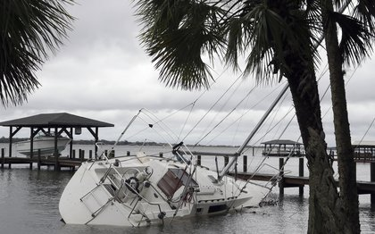 A sailboat takes on water as she sits on her side in the Indian River Friday, Oct. 7, 2016, in Rockledge (AP)