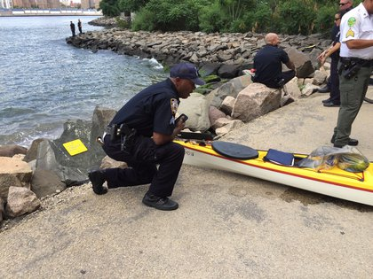 An NYPD Harbor Unit police officer inspects the kayak (Jen Chung / Gothamist)