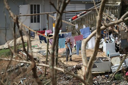 A man hangs laundry up as people wait for the electrical grid to be repaired on Sunday, September 24th in Progreso Barrio Pulguillas, Puerto Rico. (Joe Raedle/Getty Images)