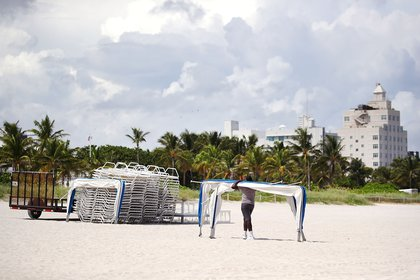 A concessioner worker removes beach awnings in preparation for approaching Hurricane Irma on September 6, 2016 in Miami Beach. (Photo by Mark Wilson/Getty Images)