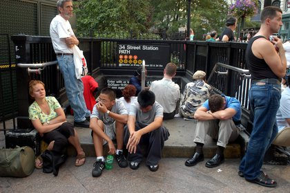 People sitting outside a closed subway station (Shutterstock)