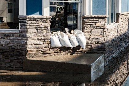 Sandbags protect a shop's doorway on 102nd Street in Howard Beach<br/>