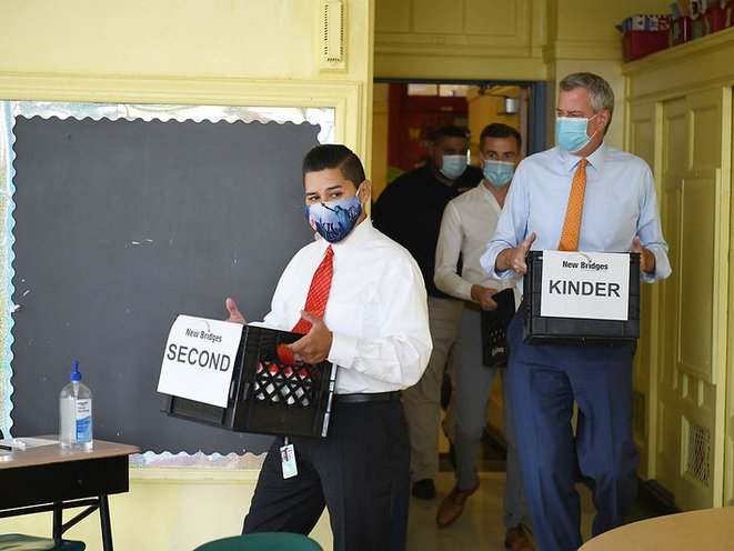 Mayor Bill de Blasio (right) and Schools Chancellor Richard Carranza (center) tour New Bridges Elementary in August to observe the school's PPE delivery and reopening preparations.