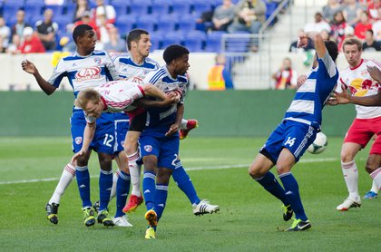 Dax McCarty goes horizontal while attempting to head a ball towards goal.