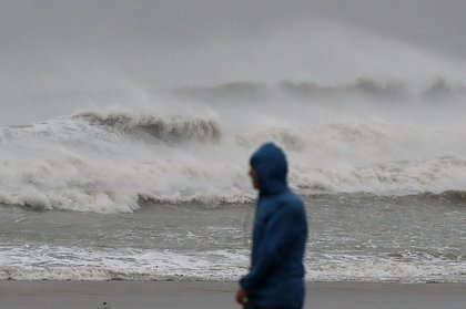 A man walks past heavy surf caused by Hurricane Matthew, October 7, 2016 on Cocoa Beach (Getty Images)