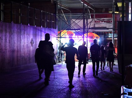 People walking under scaffolding during the power outage on July 13 (Erik Pendzich/Shutterstock)
