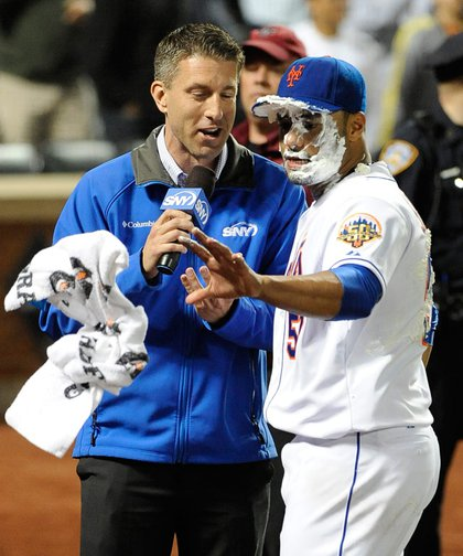 Santana reaches for a towel to wipe shaving cream off his face as he is interviewed by ESPN's Kevin Burkhardt