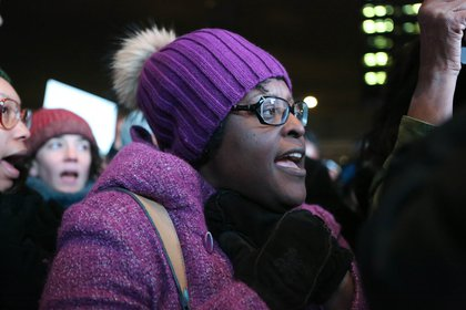 A protestor outside the Barclays Center mimics choking during a demonstration against the police killing of Eric Garner.<br>