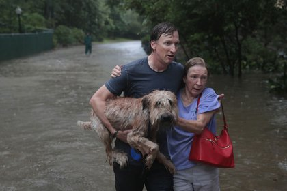 Andrew White (L) helps a neighbor down a street after rescuing her from her home in his boat in the upscale River Oaks neighborhood after it was inundated with flooding from Hurricane Harvey on August 27, 2017 in Houston, Texas.<br>(Getty Images)