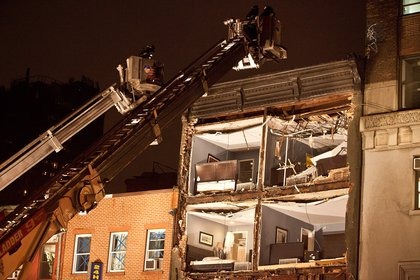 Fire fighters evaluate the scene of an apartment building which had the front wall collapse due to Hurricane Sandy on October 29, 2012 <br/>