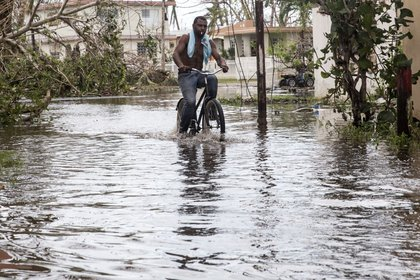 A man rides a bike through high water in Loiza, Puerto Rico, on Friday, September 22. (Alex Wroblewski/Getty Images)
