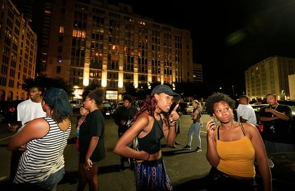Dallas residents stand near the scene where Dallas police officers were shot and killed on July 7, 2016  (Getty Images)
