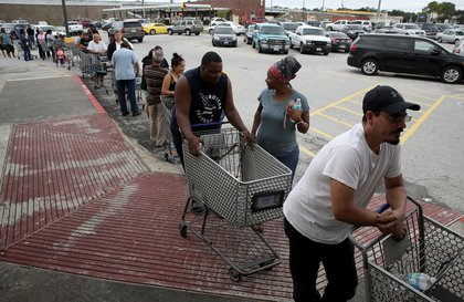 People line up to buy groceries in the Chanelview section of Houston as flood waters began to recede following Hurricane Harvey August 29, 2017.<br>