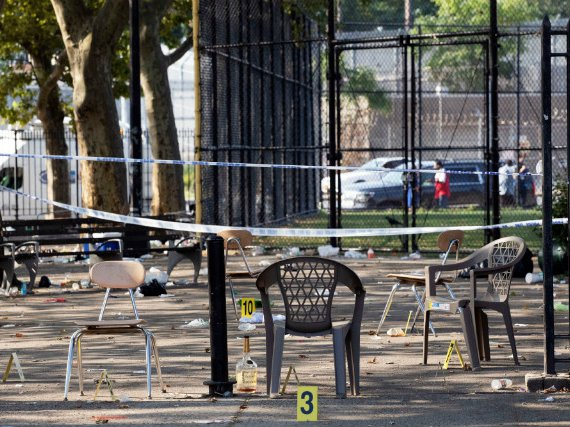 Yellow evidence markers are placed next to chairs at a playground in the Brownsville neighborhood in the Brooklyn borough of New York after Saturday night's shooting