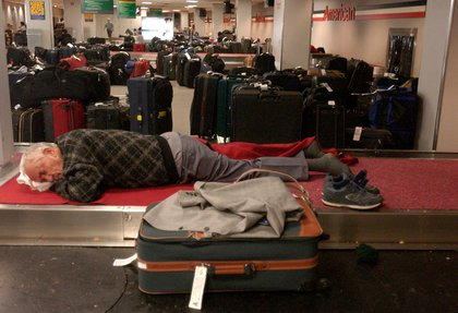 A stranded passenger sleeps on the luggage area at JFK Airport (Julie Jacobson/AP/Shutterstock)