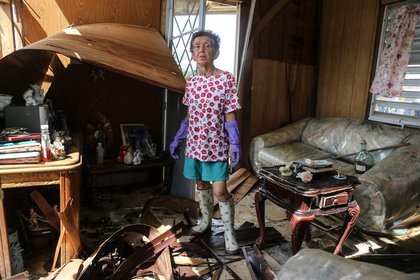 Sonia Torres, 60, poses in her destroyed home while taking a break from cleaning, three weeks after Hurricane Maria hit the island, on October 11, 2017 in Aibonito, Puerto Rico. <br/>