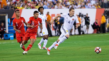 Colombia's Santiago Arias (4) advances the ball while Peru's Miguel Trauco (6) and Edison Flores (20) give chase.