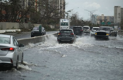 Vehicles drive along a flooded road after Hurricane Maria passed through the area on Saturday, September 23rd in San Juan, Puerto Rico. (Joe Raedle/Getty Images)