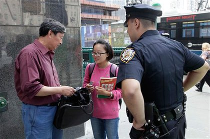 A New York City police officer stops Xiang Mao, left, and Lexi Li along the perimeter of the World Trade Center, Thursday, Sept. 8, 2011 in New York. The officer's hand-held radiation detector indicated that one of the two may have had radioactive material. Xiang Mao explained that he had been injected with radioactive material for medical tests Wednesday. The two tourists from Canton, China were allowed to continue on their way.
