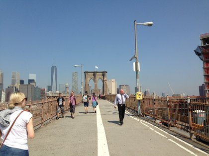 Detective, on the right, with white flag Brooklyn Bridge behind him (Jen Chung/Gothamist)