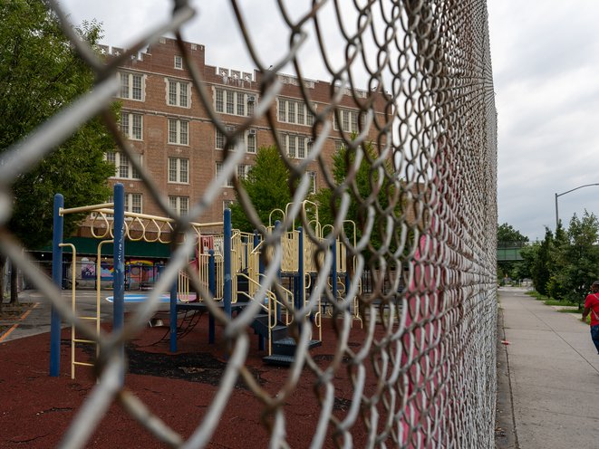 The exterior of Bronx Elementary School 75, seen through chain link fence, playground