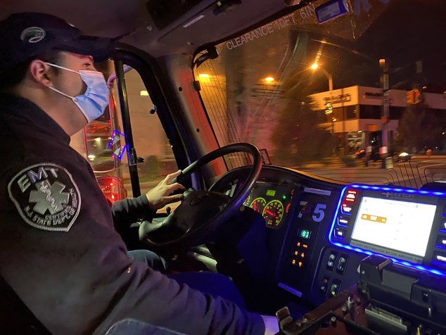 Finklestein, in a mask, drives the ambulance
