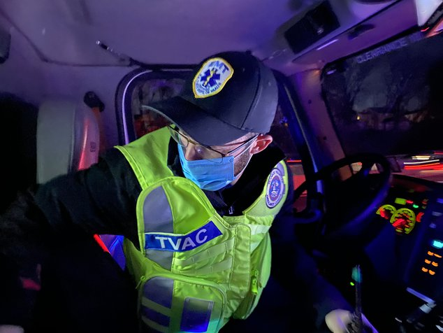 Rimberg, in a hat and PPE, reaches in his ambulance