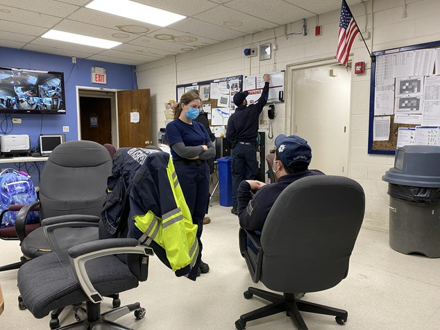 Members of the EMT group are in their office, sitting in chairs or standing.
