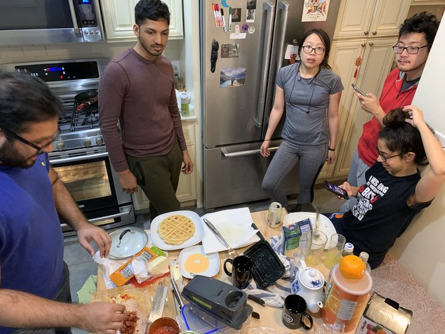 people in a kitchen surrounding a table of food