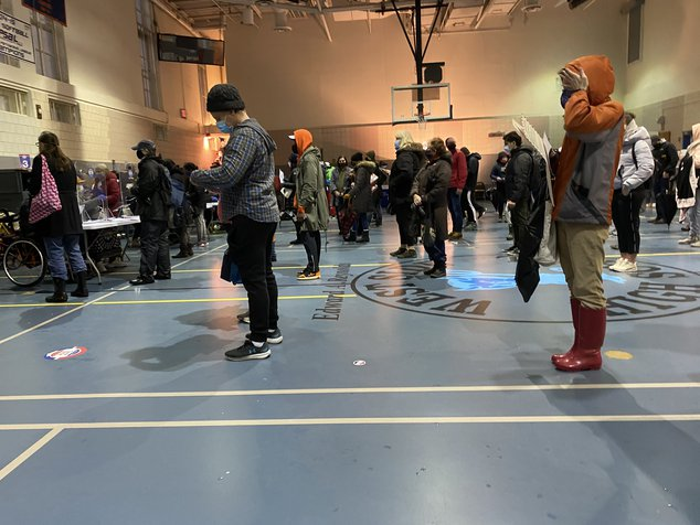 Lines of people waiting to check into West Side High School early voting, at the tables where poll workers print out ballots
