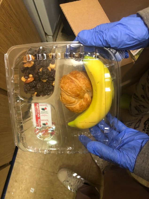 Meal including a banana and a croissant in plastic packaging, held by a person wearing gloves