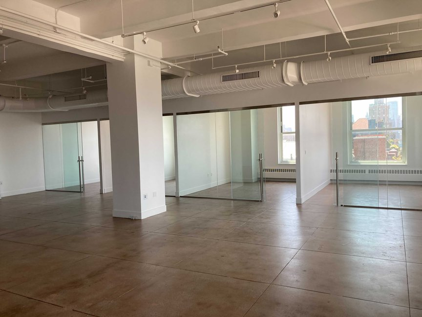 A renovated floor shows shiny wood floors and modern-looking glass partitions on an unoccupied, recently renovated space