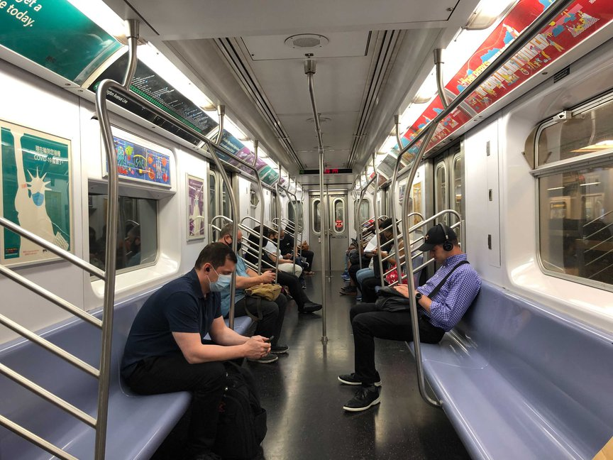 About six subway riders, all masked, on a train