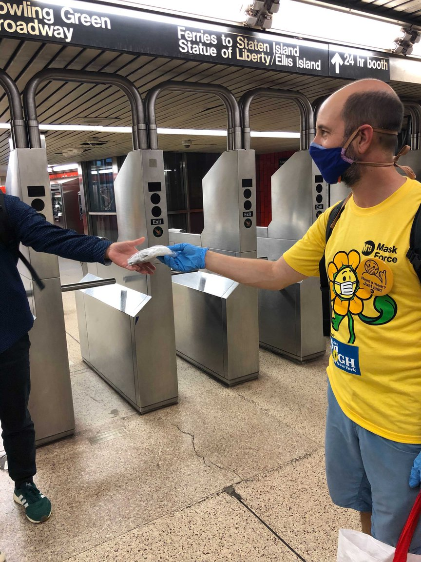 Stephen Nessen, who is wearing a bright yellow Mask Force t-shirt with a masked flower on it, hands out a mask to a subway rider near turnstiles